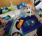 Auf einem Tisch liegen Kleber und Stoffe mit denen Kinder an einer Collage arbeiten. Die Collage hat die Form eines Gesichts.